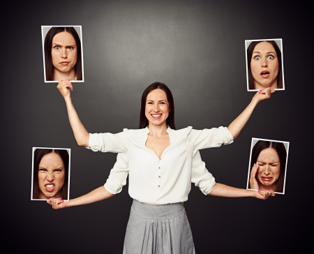 emotions faces: smiley woman with four hands holding pictures with different emotional faces Stock Photo