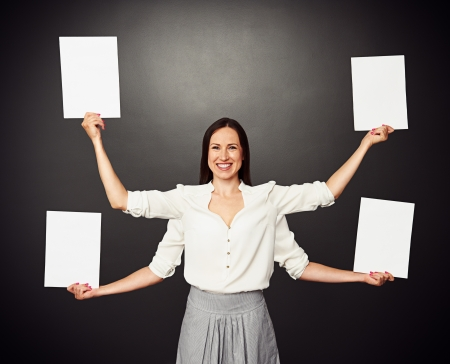 smiley woman with four hands holding white empty boards photo