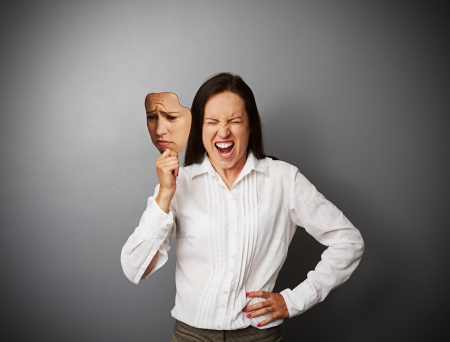 dissimulation: young businesswoman hiding her anger behind the mask of sad mood Stock Photo