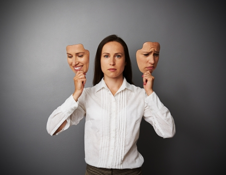 dissimulation: young businesswoman woman holding two masks with different mood Stock Photo