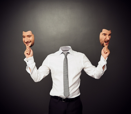 dissimulation: faceless man holding masks with good and bad moods