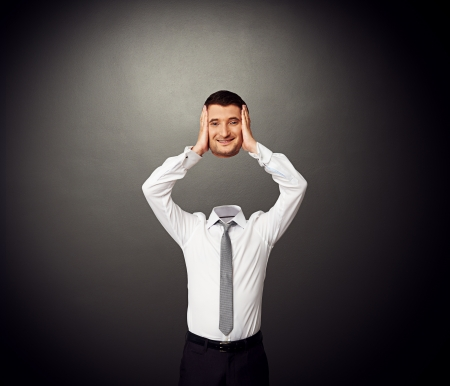 estrange: businessman holding his smiley head in hands. photo over dark background