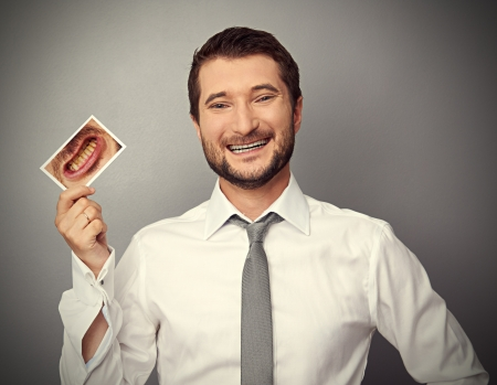 stomatologist: smiley healthy man holding picture with dirty yellow teeth