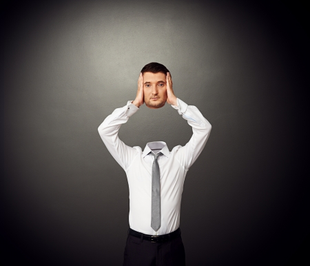 cut off head: businessman with the severed head in his hands Stock Photo