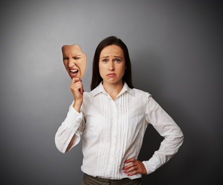 dissimulation: sorrowful woman holding mask with bad mood