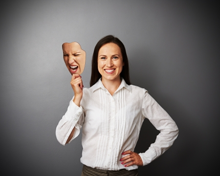 dissimulation: smiley woman holding mad mask Stock Photo
