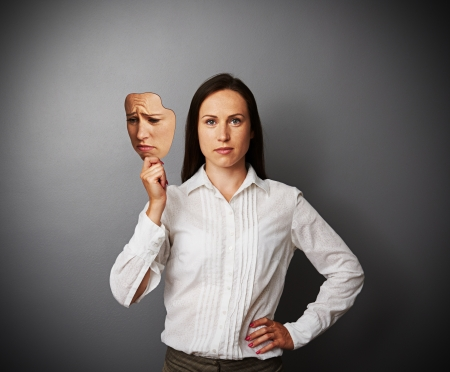 disillusionment: young woman holding sad mask Stock Photo