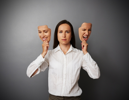 serious woman holding two masks with different mood Stock Photo - 20147195