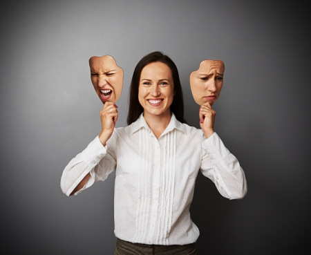 masks: young beautiful woman hiding her good mood under masks Stock Photo