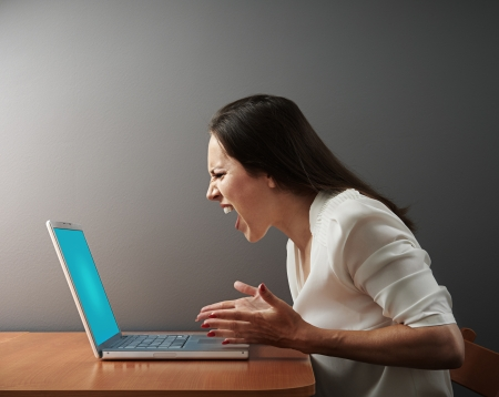 mujer enojada: gritando mujer enojada con el ordenador portátil