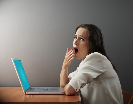 tedious: boring woman sitting with laptop and yawning