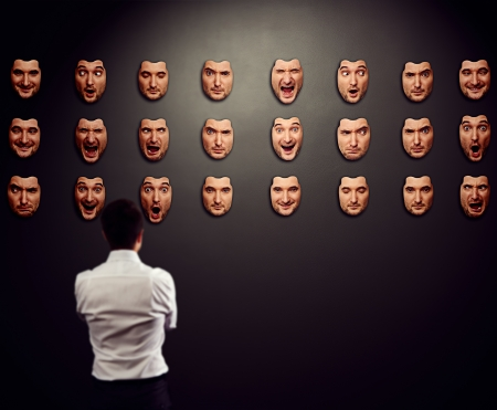 businessman looking at mask and selecting his mood photo