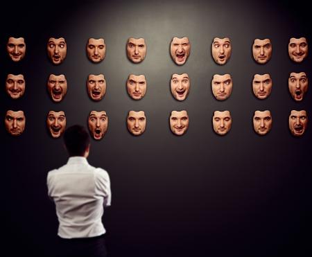 zakenman op zoek naar masker en het selecteren van zijn stemming Stockfoto