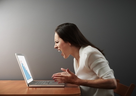 angry women: angry businesswoman looking at negative statistic Stock Photo