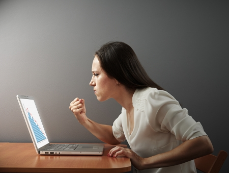 angry businesswoman looking at negative statistic and showing fist photo