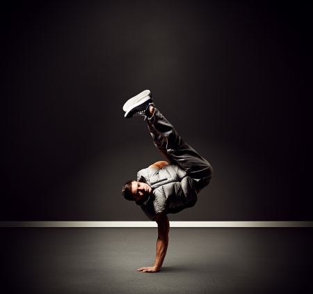 aerobica: cool young dancer standing on the freeze over dark background