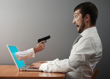 startled: concept photo of digital robbery. man afraid of hand with gun