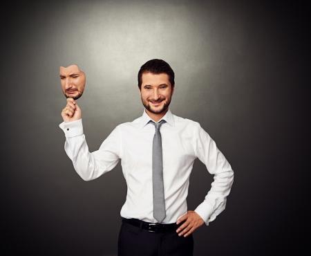 cara triste: hombre de negocios sonriente sosteniendo m�scara triste sobre fondo oscuro