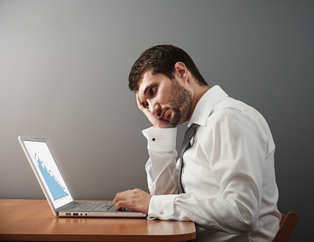 sorrowful: sorrowful businessman looking at his laptop