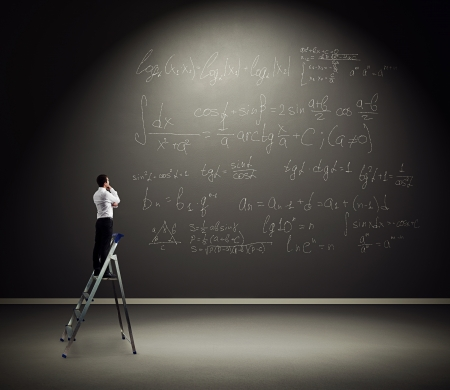adult classroom: serious man standing on the stepladder and pondering over formulas