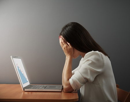depressed woman covering her face by the hands over dark wall photo