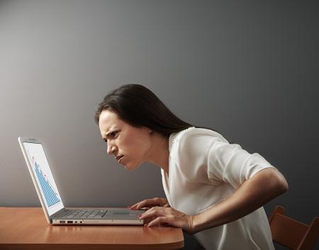 desconfianza: mujer joven que busca en la computadora portátil con la desconfianza