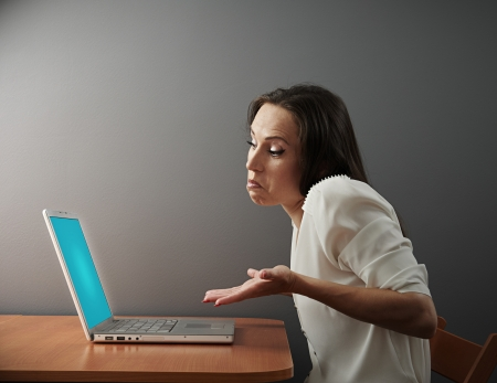 misunderstanding: businesswoman looking at laptop with misunderstanding