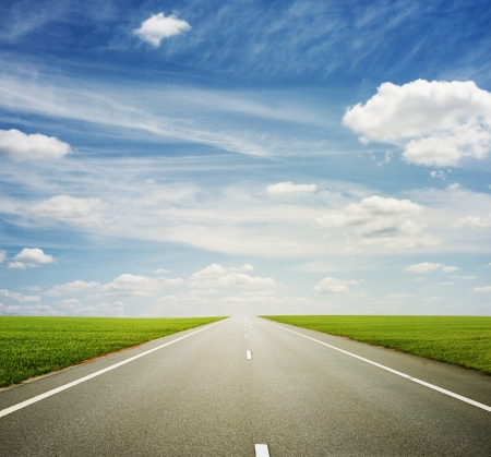 beautiful view of roadway, green field and blue sky Stock Photo