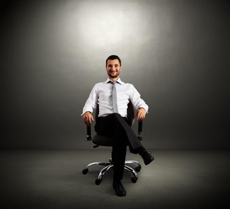 hombre: jefe exitoso sentado en la silla contra la pared gris