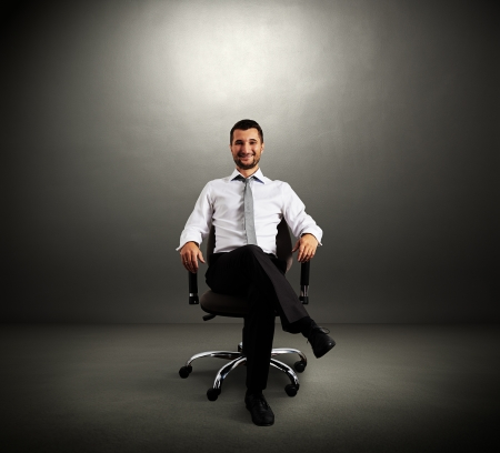 successful boss sitting on chair against grey wall photo