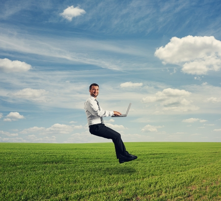 flying man: successful businessman working with laptop and hover over green field Stock Photo