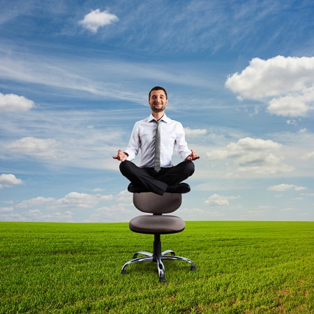 happy businessman is meditating and hovering over chair