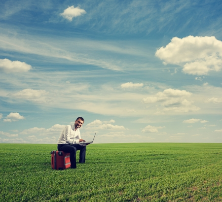 distant: young smiley businessman working with laptop at the green field Stock Photo