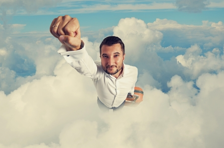 super hero businessman with suitcase flying through the clouds Stock Photo