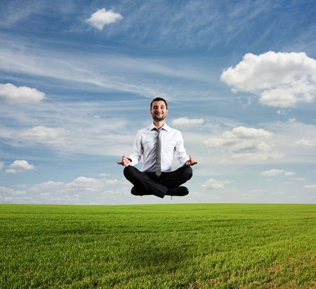 happy businessman in formal wear hover over green field
