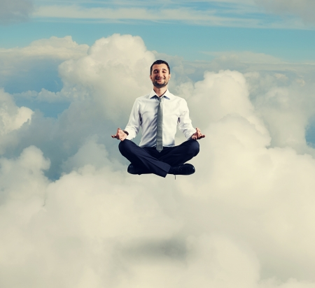 hover: happy businessman in formal wear meditating in the sky