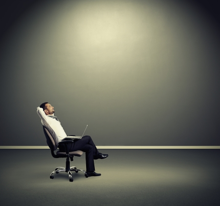 SATISFIED: satisfied businessman resting on the chair