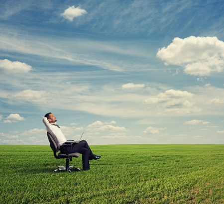 resting: smiley businessman resting on the green field Stock Photo