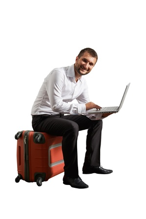 distant work: smiley businessman sitting on suitcase and working with laptop. isolated on white background