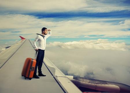 plan éloigné: jeune homme d'affaires debout sur l'aile d'un avion