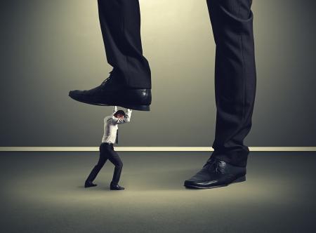 downtrodden: small businessman under big leg his boss Stock Photo