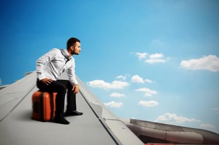 plan éloigné: homme d'affaires sérieux assis sur son sac et voler sur l'aile d'un avion