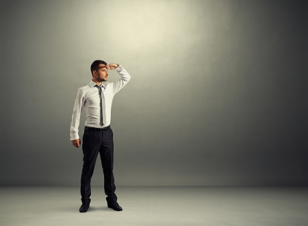 forward: serious man standing in dark room and looking forward Stock Photo