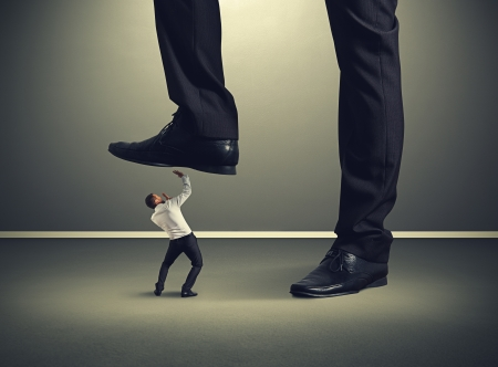 scared small businessman under big leg his boss Stock Photo