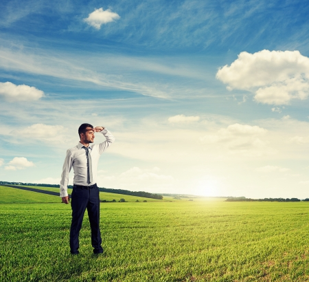 distant: serious and thoughtful businessman standing on green field and looking forward Stock Photo