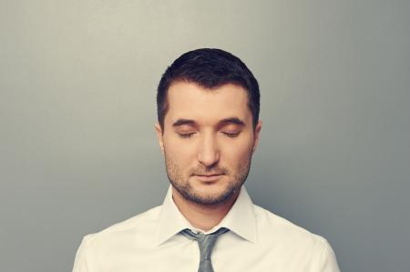 目を閉じて灰色の背景上のビジネスマンの肖像画 写真素材