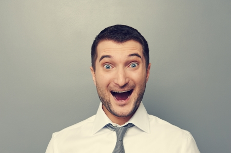 excited man: portrait of excited businessman over grey background