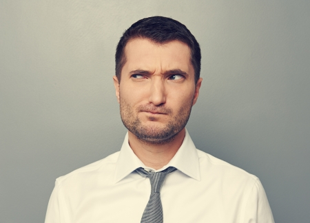 discredit: portrait of thoughtful man over grey background