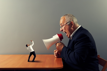 reprimand: senior boss screaming at small businessman Stock Photo