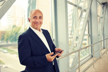 old pc: serious businessman holding tablet pc and looking at camera